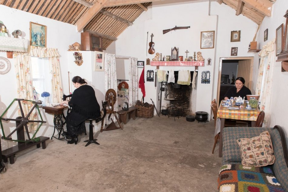 Interior view of one of the cottages at Glencolmcille Folk Village, with women weaving in the old tradition.